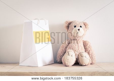 Teddy bear and paper bag on wooden table