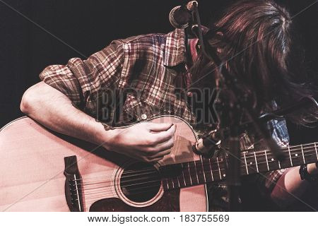 Man strumming an acoustic guitar while performing on stage.