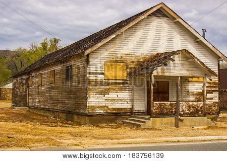 Old Weathered Building With Boarded Up Windows & Doors