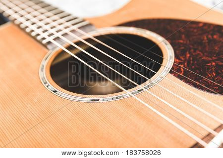 Close up of steel strings on an acoustic guitar. Cedar top with textured pickguard and ornate design around sound hole.