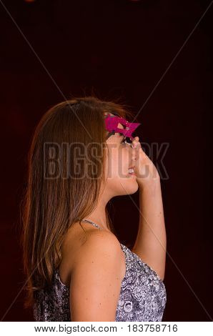 Beautiful model woman wearing pink carnival mask over her fore.