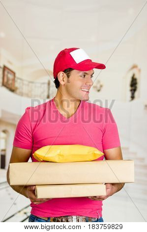Delivery man in pink uniform holding boxes and documents