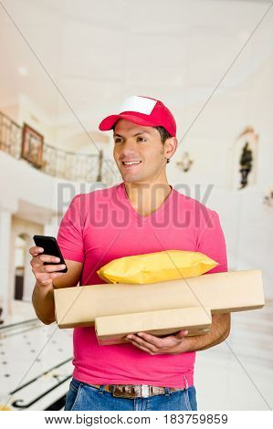Delivery man in pink uniform holding boxes and documents getting ready to Sign papers