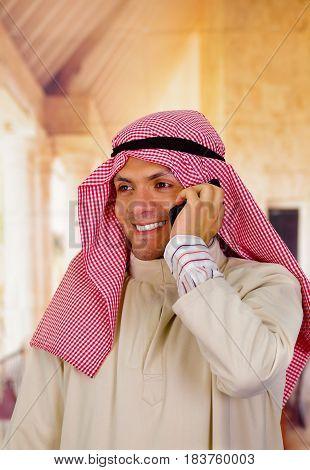 smiling cute arabian man using his cellphone.