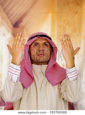 Cute young arabian guy praying to god.