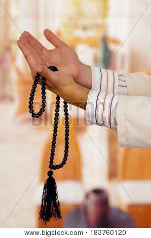 Arabian guy praying to his god and holding a masbaha.
