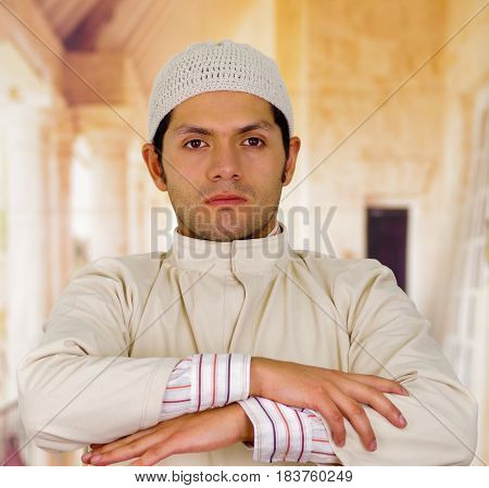 serious cute arabian man with arms crossed.