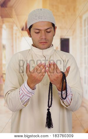 Cute arabian guy holding a masbaha with his hands.