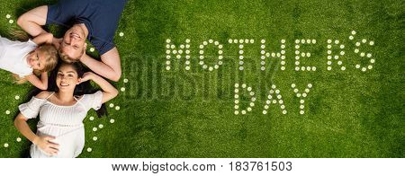 Young family laying in the grass on mothers day