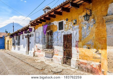 Antigua, Guatemala - April 13 2017: Old colonial houses with purple Lent banners hanging in the windows & Agua volcano behind in colonial city & UNESCO World Heritage Site of Antigua, Guatemala, Central America