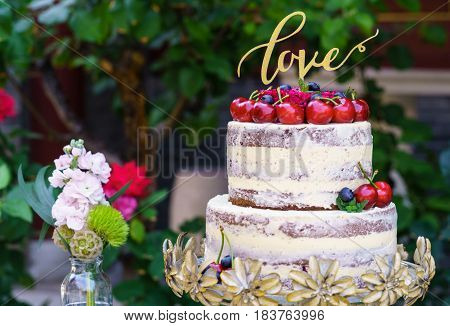 Multilayered wedding cake covered in white icing sugar and decorated with rosy red apples placed on a stand outside in the garden next to a flowering shrub. On top of the cake in gold is the word