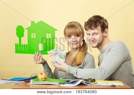 Family future ownership financial bank property home concept. Young couple managing finances. Girl and boy counting money showing house symbol.