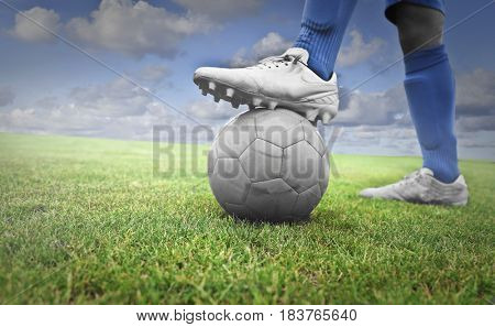 Footballer in a green field holding a ball with his foot