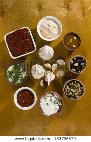 Various sauces with garlic on a wooden surface
