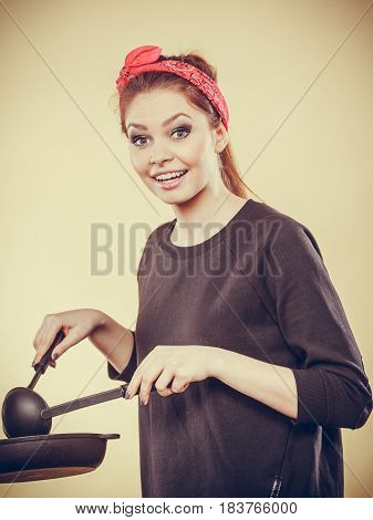 Preparing food concept. Retro styled girl trying to do something to eat on frying pan. Woman cooking dinner making sauce pasta.