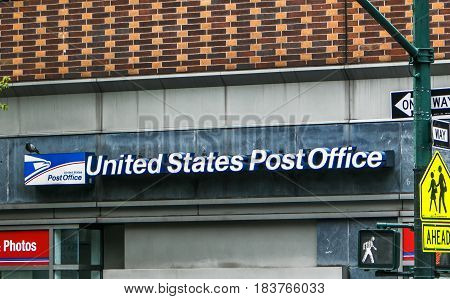 New York April 27 2017: The sign above a US Post office in Manhattan serves as a convenient resting spot for pigeons.