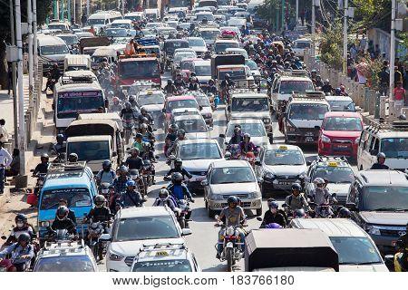 KATHMANDU NEPAL - OCTOBER 25 2016 : Traffic moves slowly along a busy road in Kathmandu Nepal. Crowded traffic jam road in city