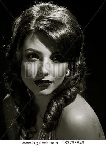 woman studio portrait in hollywood style light on black background. in black and white toning