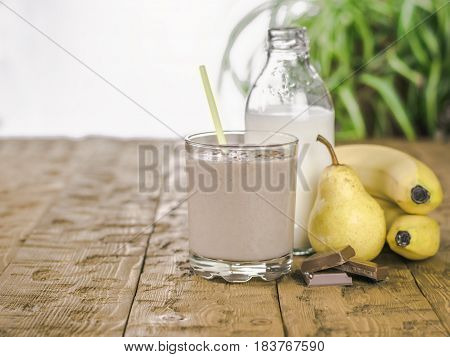 Banana smoothie with chocolate pear and milk on a wooden table. The concept of a healthy diet.