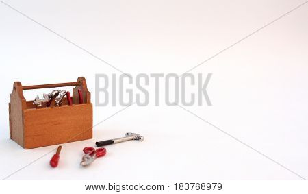 Miniature tool box on wood slats and white background.