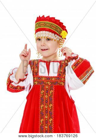 Cute little girl in Russian folk dress. She threatens with a finger.Isolated on white background.