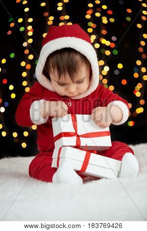 baby unpack gift boxes with christmas decoration, dressed as Santa, boke lights on dark background, winter holiday concept