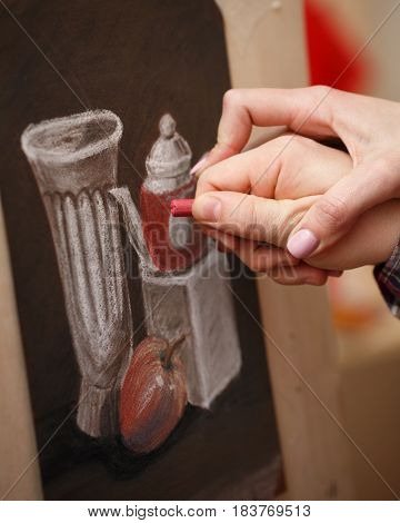 The man paints a still life pastel crayon at the art school. The teacher helps to correct the defects in the picture. Hands close-up. Courses of drawing for adults.