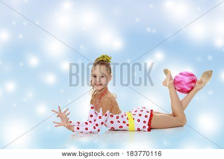 Beautiful little girl gymnast dressed in sports suits for competition, performs exercises with the ball.Blue Christmas festive background with white snowflakes.