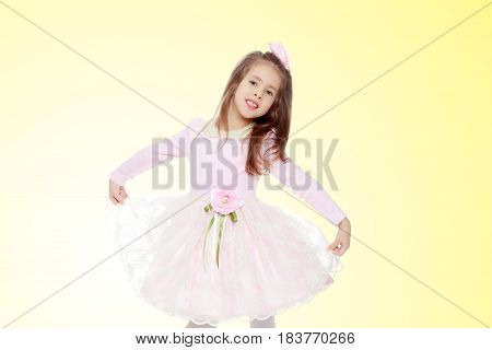 Dressy little girl long blonde hair, beautiful pink dress and a rose in her hair.It stretches over the edges of the dress.On a yellow gradient background.