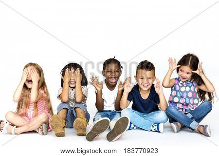 Diverse group of children doing peek a boo hand gesture