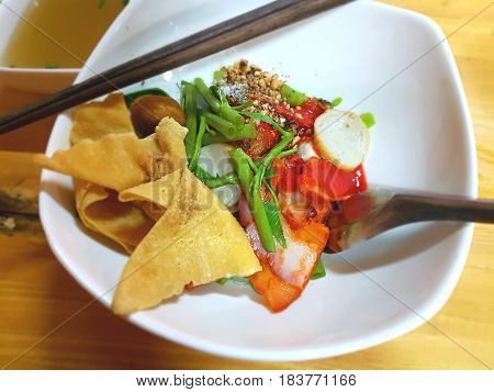Thai-style food, dry noodles with fish balls, crispy won ton skin, and red sauce.