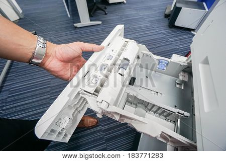 close up businessman pull office printer tray for input paper sheet