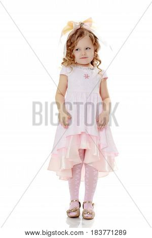 Beautiful, chubby little girl with long, blond, curly hair.Dressed in a pink dress and a bow in her hair.Girl shows the doll.Isolated on white background.