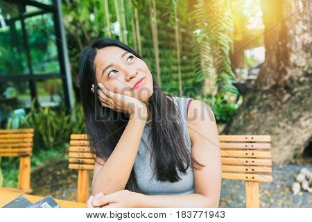 Thinking about or missing passed memory. Thai Asian women long hair hand chin rest and watching vision look out far away with sun light at cafe