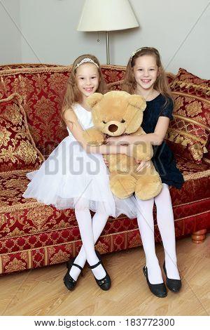 Two adorable little twin girls sitting on sofa hugging a big Teddy bear.