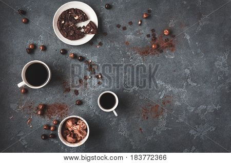 Cups of coffee chocolate cake and chocolate ice cream on dark background. Flat lay top view copy space