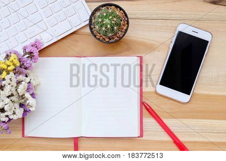 Office desk table with keyboard, notebook, pen and dry bouquet flower. Top view with copy space