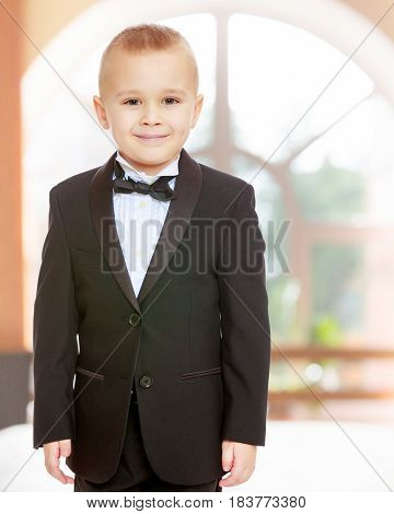 Beautiful little blond boy in a fashionable black suit with a tie.In a room with a large semi-circular window.