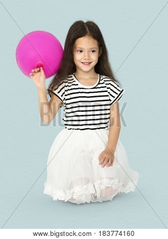 Young girl is sitting holding pink balloon