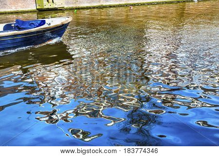 Blue Boat Reflection Singel Canal Amsterdam Holland Netherlands. Canals in Amsterdam create beautiful abstract reflections.