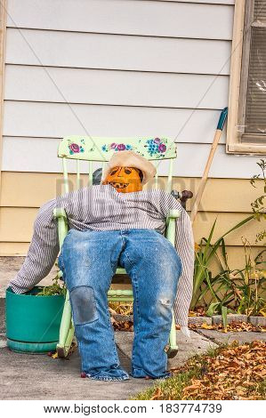 Stuffed man in tattered blue jeans with a striped shirt and pumpkin face resting in a rocking chair