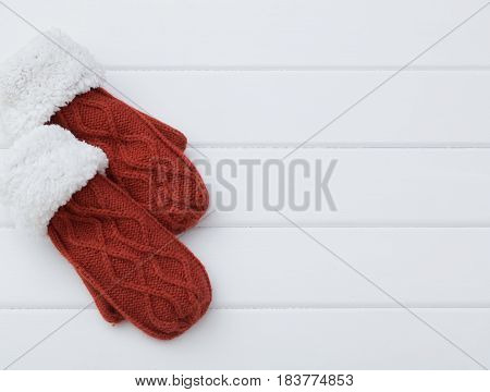 the red mittens on old wooden background