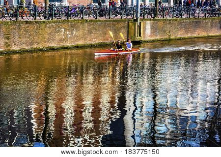 AMSTERDAM, NETHERLANDS - MARCH 30, 2017 Kayak Rowing Reflection Singel Canal Amsterdam Holland Netherlands. Canals in Amsterdam create beautiful abstract reflections.