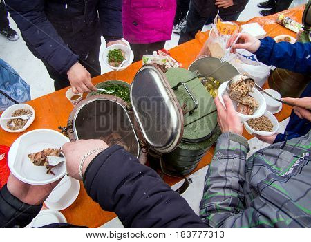 Murmansk, Russia - April 09, 2017: Distribution of hot food from army thermos to needy residents