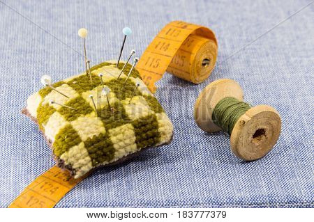 Jeans fabric for sewing, accessories for needlework on new jeans background. Spool of thread, scissors, thimble, tapemeasure , sewing supplies. Set for needlework top view