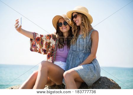 Smiling female friends taking selfie while sitting on rock at beach against sky