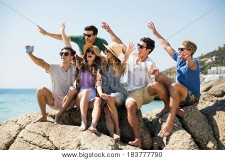 Young friends taking selfie while sitting on rock formations at beach during sunny day