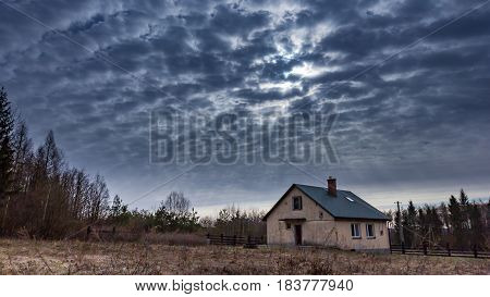 Landscape with house at day under cloudy sky. Spooky landscape with house in cloudy dull day.