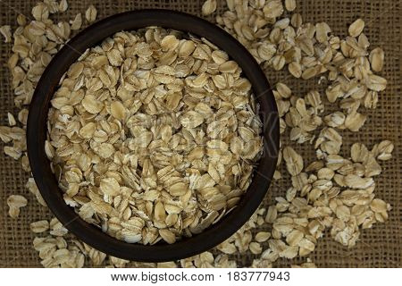Dry oat flakes oatmeal in bowl on sacking