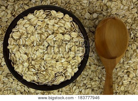 ry oat flakes oatmeal in bowl on the background with wooden spoon